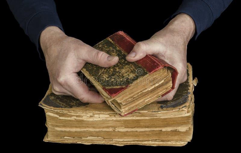 Die Hände der Männer halten das alte Buch stockfoto