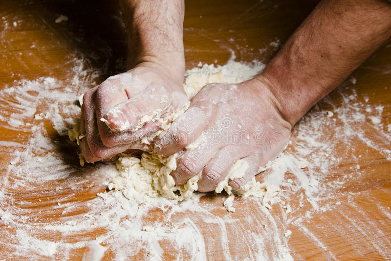 Die Hände der Männer kneten den Teig auf dem Holztisch lizenzfreies stockfoto