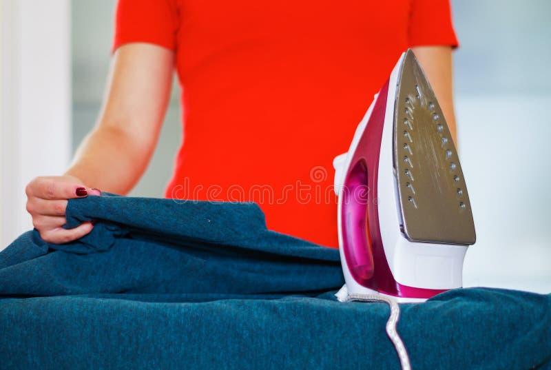 Die Hände der Nahaufnahmefrau unter Verwendung des bügelnden Gerätes auf blauem Gewebe, Wäschereihausarbeitkonzept stockfoto