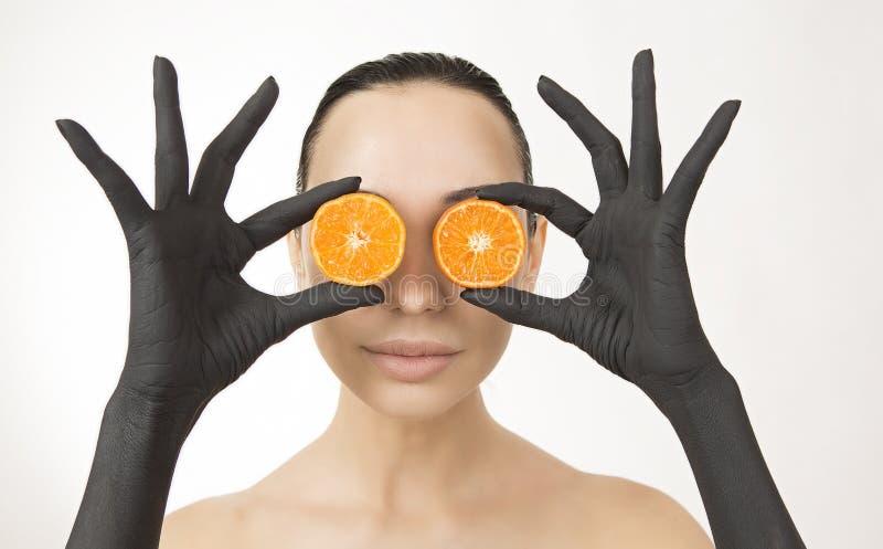 Die Hände der schwarzen Frau, die orange Hälften nahe ihrem Gesicht halten Schwarze Hände mit heller geschmackvoller Mandarine lizenzfreie stockfotografie