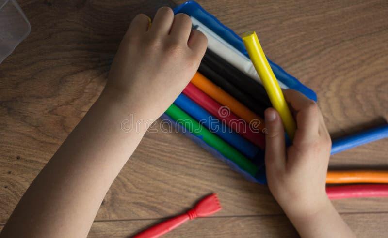 Die Hände des kleinen Mädchens den mehrfarbigen Lehm herausnehmen lizenzfreies stockbild