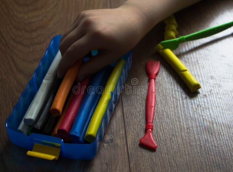 Die Hände des kleinen Mädchens den mehrfarbigen Lehm herausnehmen lizenzfreies stockfoto