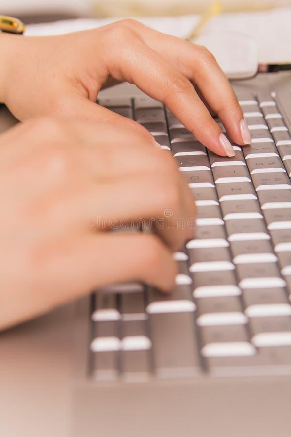 Die Hände des Mädchens, die auf einer Laptoptastatur schreiben stockfotos