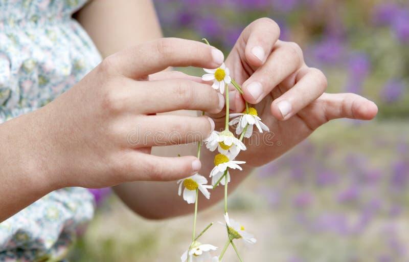 Die Hände des Mädchens, die Blumen-Halskette machen stockfotos
