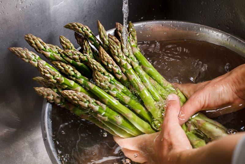 Die Hände des Mannes, die Spargel waschen stockfotos