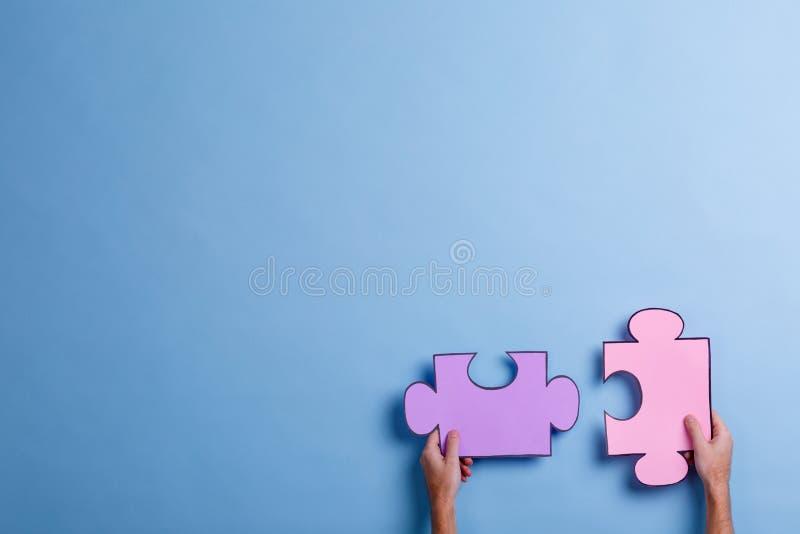 Die Hände des Mannes halten große rosa und lila Farbpuzzlespiele Blauer Hintergrund mit einem Platz für eine Aufschrift lizenzfreies stockfoto