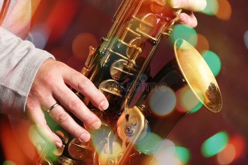 Die Hände des Mannes mit Saxophon auf bokeh Lichtern lizenzfreie stockbilder