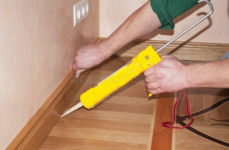 Die Hände des Schlossers, die Fussleiste-Eichen-Bretterboden mit dem Kalfatern von GU installieren stockfoto