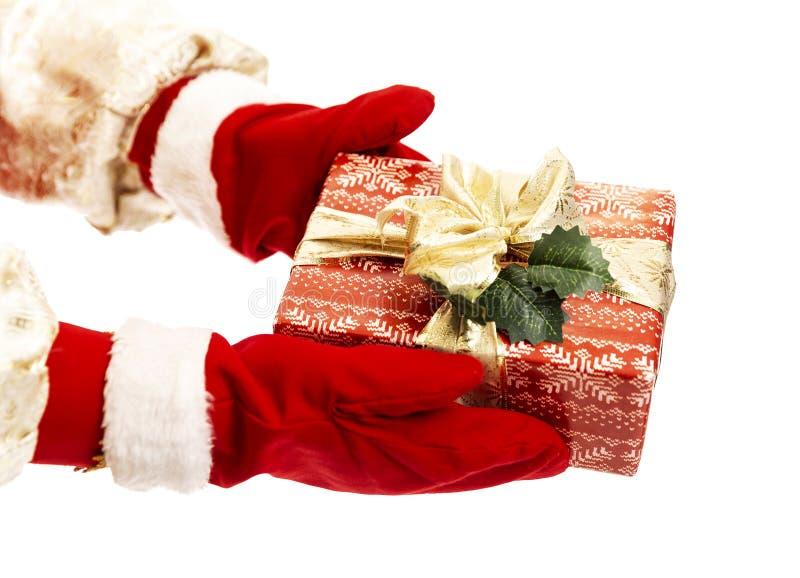 Die Hände des Weihnachtsmanns in den Rotmilbenfäusten haben ein Geschenk in rotem Papier mit goldenem Bugbogen Glückwünsche zum n lizenzfreies stockbild