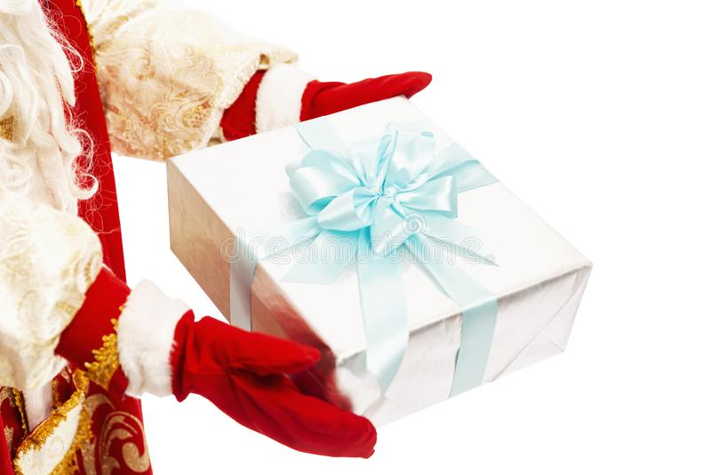 Die Hände des Weihnachtsmanns in den Rotmilbenfäusten tragen ein Geschenk in Silberpapier mit blauem Bogen Glückwünsche zum neuen stockbild