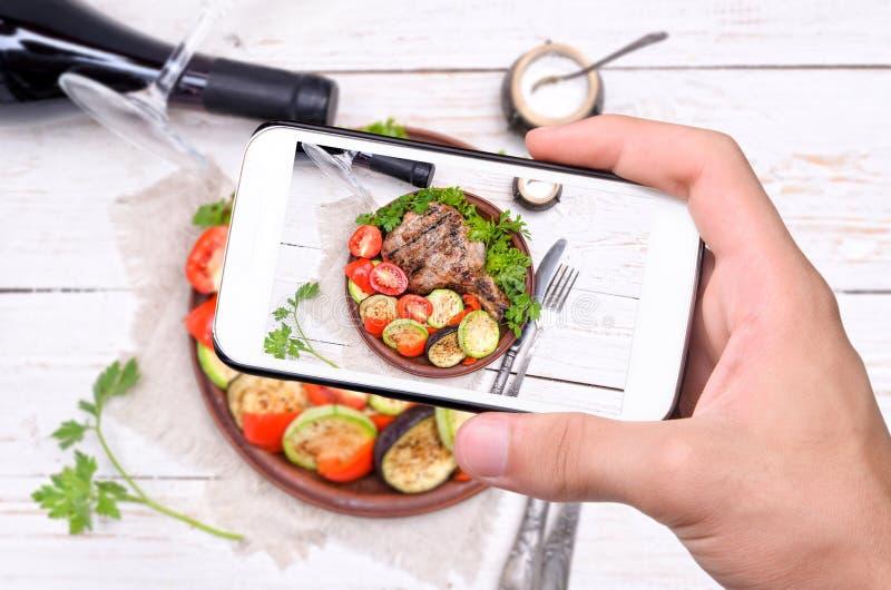 Die Hände, die Foto machen, grillten Rippe mit gegrilltem Gemüse mit Smartphone lizenzfreie stockfotos