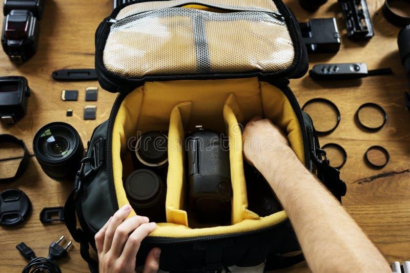 Die Hände, die ein Kamerataschenvorbereiten halten, setzten eine Ausrüstung herein stockfotografie