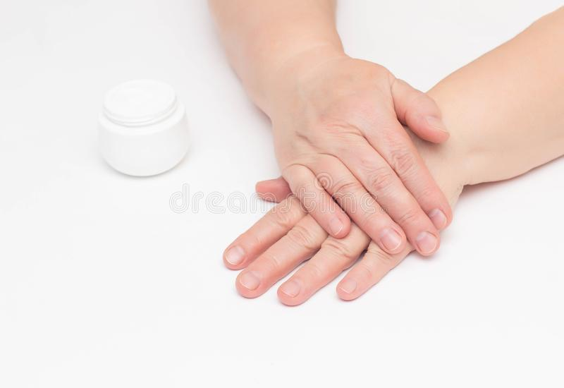 Die Hände einer älteren Frau auf einem weißen Hintergrund und der komplexen Creme mit Vitamin gegen Falten und Enge an lizenzfreies stockfoto