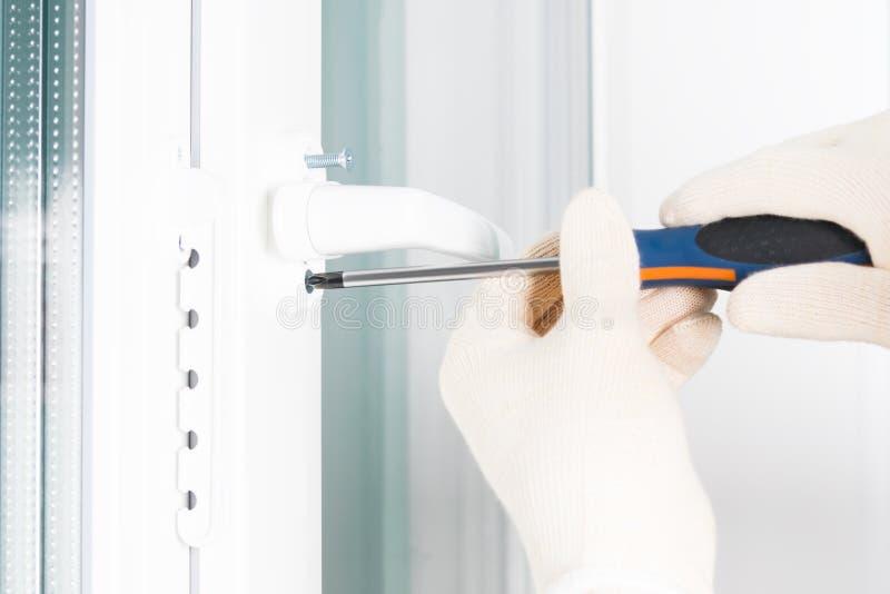 Die Hände eines Arbeitnehmers befestigen den Griff an ein Kunststofffenster, seitliche Nahaufnahme lizenzfreie stockbilder