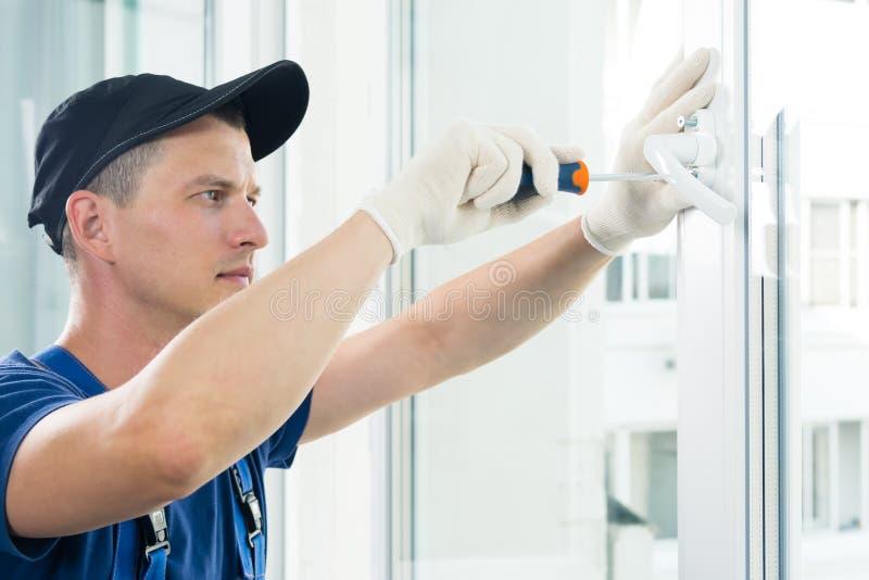 Die Hände eines Arbeitnehmers befestigen den Griff an ein Kunststofffenster, seitliche Sicht stockfoto