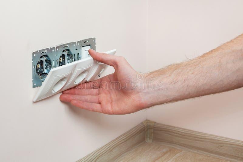 Die Hände eines Elektrikers, der eine WandNetzdose installiert lizenzfreie stockfotos