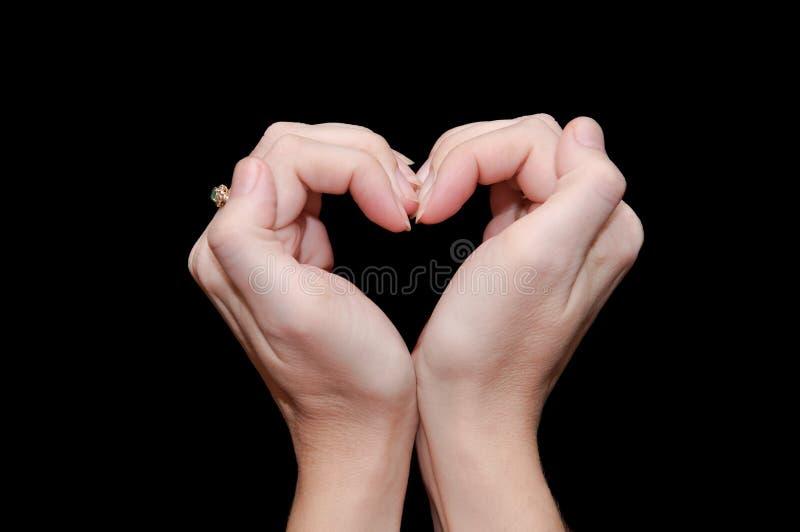 Die Hände falteten Herz stockbild