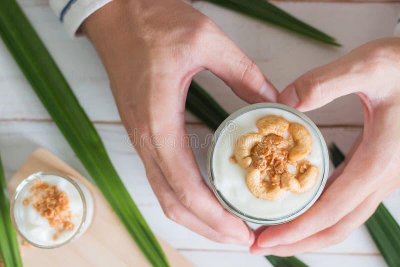 Die Hände, die gesunde Mahlzeit gemacht vom Granola im Glas, im Jogurt und in den Corn-Flakes halten, verzieren Nahrung mit Acajo stockfoto