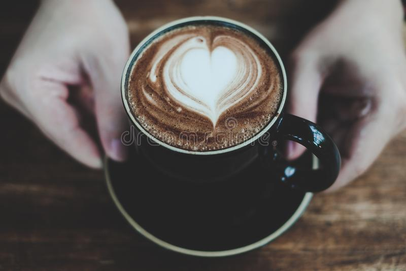 Die Hände, die Schale heißen Kaffee mit Herzen halten, formten Schaum, warmen Farbton lizenzfreies stockfoto