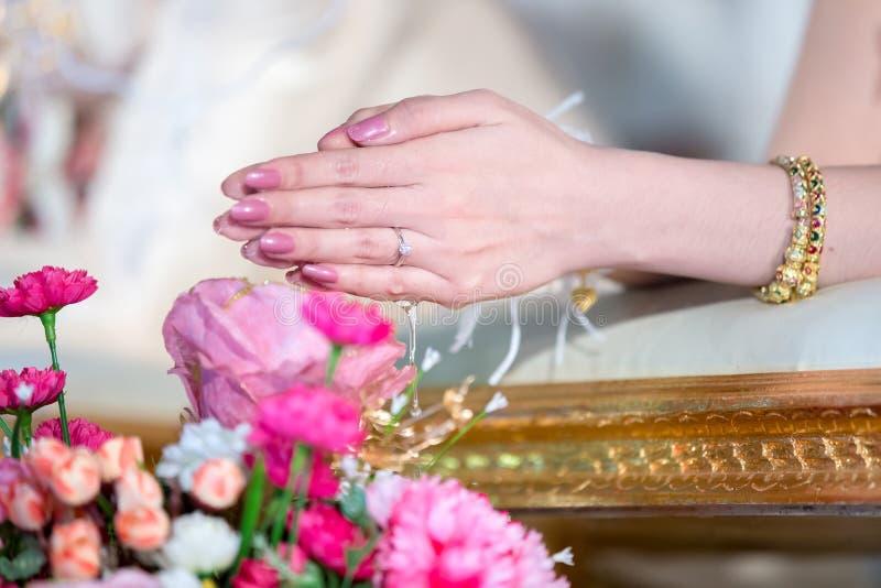 Die Hände, die Segen gießen, wässern in Braut ` s Bänder, thailändische Hochzeit lizenzfreies stockfoto