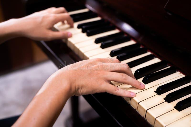 Die H?nde von zwei Handfrauen sitzen in der Presse, das alte braune Klavier ist gl?cklich stockbilder