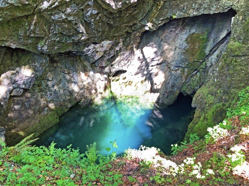 Die Höhle und die Quelle Hundsloch durch den alpinen See Wagitalersee oder Waegitalersee, Innerthal stockfotos
