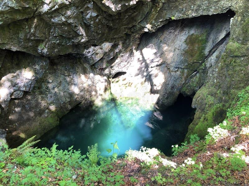 Die Höhle und die Quelle Hundsloch durch den alpinen See Wagitalersee oder Waegitalersee, Innerthal lizenzfreies stockfoto