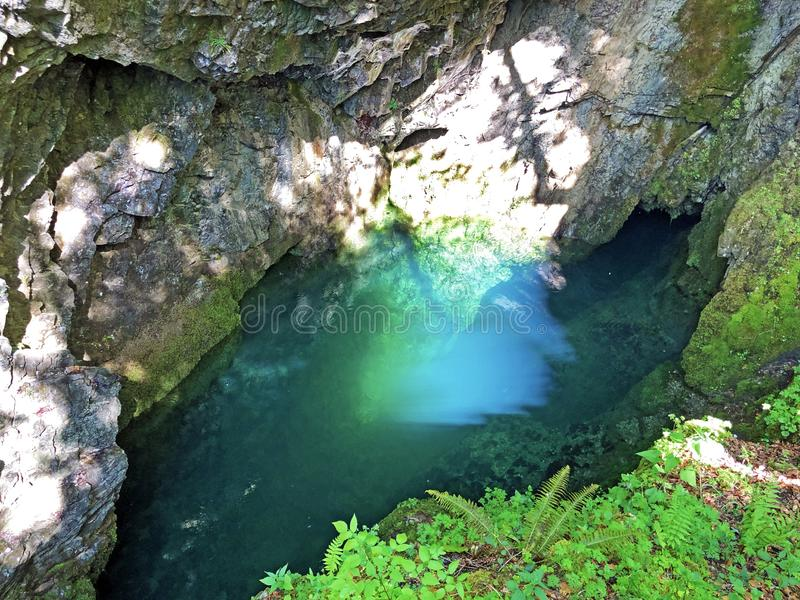 Die Höhle und die Quelle Hundsloch durch den alpinen See Wagitalersee oder Waegitalersee, Innerthal stockbild