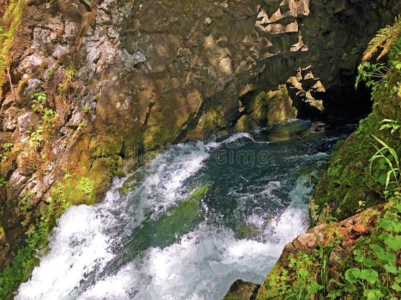 Die Höhle und die Quelle Hundsloch durch den alpinen See Wagitalersee oder Waegitalersee, Innerthal stockfotografie