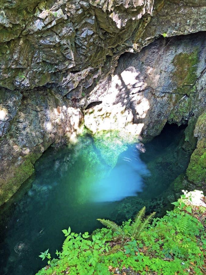 Die Höhle und die Quelle Hundsloch durch den alpinen See Wagitalersee oder Waegitalersee, Innerthal lizenzfreies stockbild