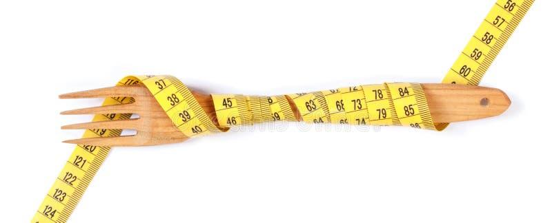 Die hölzerne Gabel, die im Zentimeter auf weißem Hintergrund, Konzept von eingewickelt wird, verlieren Gewicht und gesunden Leben lizenzfreies stockfoto
