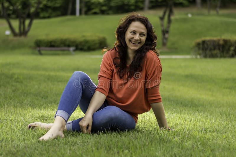Die hübsche Frau im Park auf dem Gras lizenzfreie stockfotos