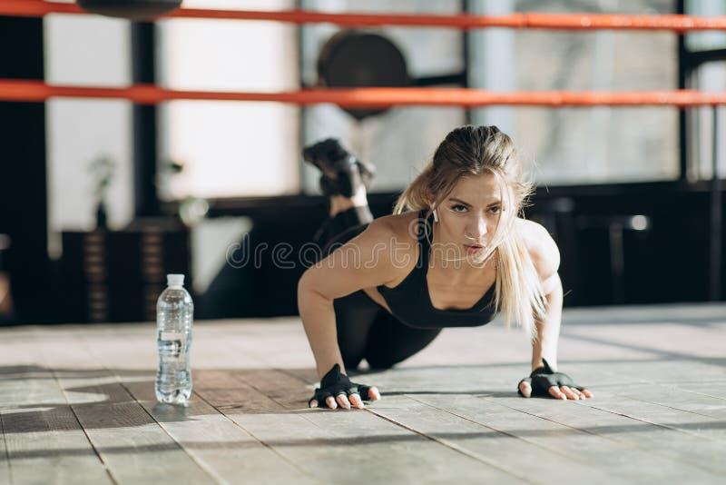 Die hübsche Frau, welche die Kamera betrachtet, beim Handeln drücken Sie, ups vom Bretterboden in der Turnhalle lizenzfreie stockfotografie