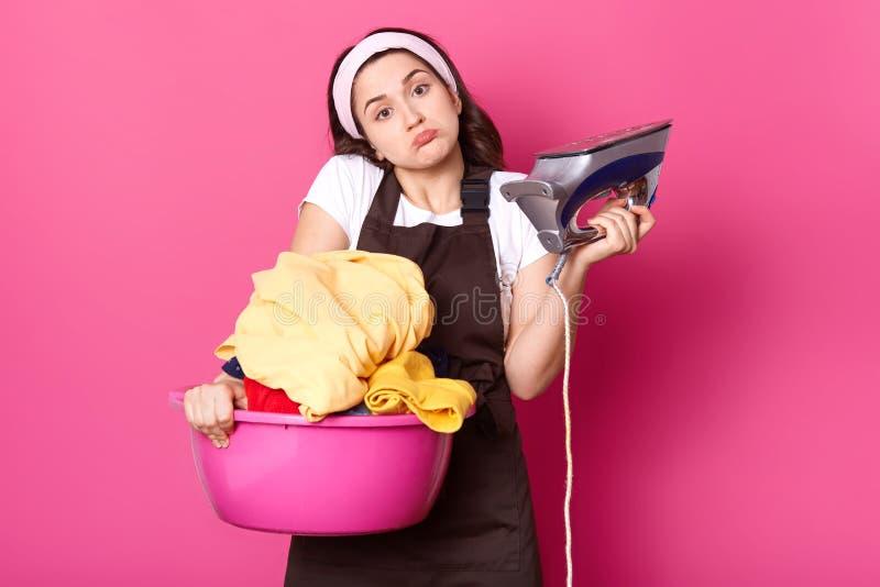 Die hübsche Hausfrau der jungen Frau, die zum Bügeln von sauberen gewaschenen Sachen bereit ist, hat Eisen, hält rosa Becken mit  stockfotografie