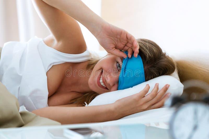Die hübsche junge Frau, die Schlafenmaske und Betrachten der Kamera nach hochzieht, wachen im Schlafzimmer zu Hause auf lizenzfreie stockfotos