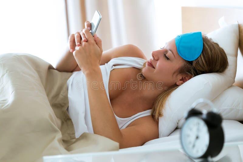 Die hübsche junge Frau, die Textnachricht mit ihrem Smartphone nach sendet, wachen im Schlafzimmer zu Hause auf stockfotos