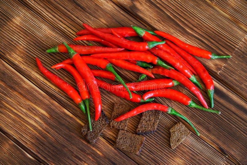 Die Hülsen von Pfeffern des roten Paprikas und von Crackern der Schwarzbrotlüge auf einer hölzernen rustikalen Tabelle von Kiefer stockfoto