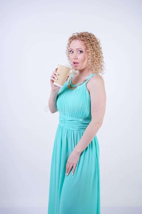 Die h?bsche blonde kaukasische Frau, die das lange blaue Sommerkleid h?lt Papiertasse kaffee tr?gt und genie?t das Leben auf wei? lizenzfreies stockbild