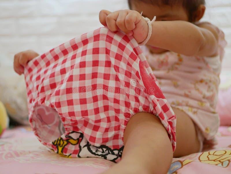 Die H?nde des kleinen asiatischen Babys, die auf kurzen Hosen, wie sie lernend, es durch an zu setzen halten stockfotos