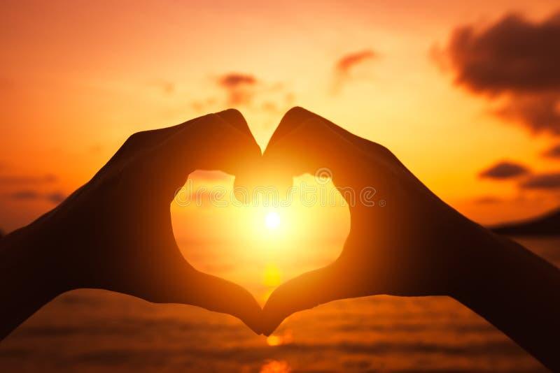 Die H?nde, die ein Herz bilden, formen mit Sonnenuntergangschattenbild lizenzfreies stockbild