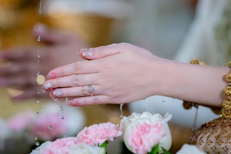 Die H?nde, die Segen gie?en, w?ssern in Braut ` s B?nder, thail?ndische Hochzeit Hochzeitszeremonie in Thailand lizenzfreie stockbilder