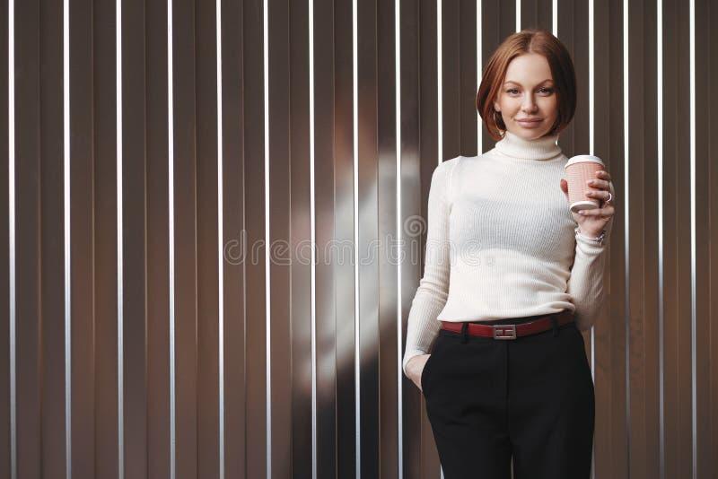 Die halbe Länge, die von der angenehmen schauenden Geschäftsfrau gekleidet wird in der Abendtoilette geschossen wird, hält Hand i stockbild