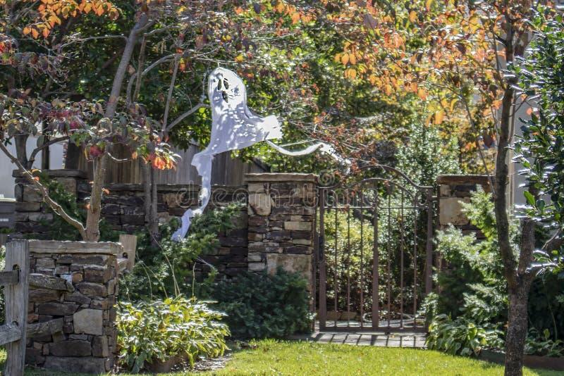 Die Halloween-Geistdekoration, die vom Baum durch Gartentor mit Sonne hängt, sprenkelte und von hokeh Herbstlaub um sie lizenzfreies stockfoto