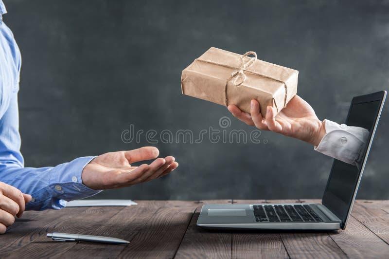 Die Hand, die aus den Laptop herauskommt, gibt das Paket stockfotos