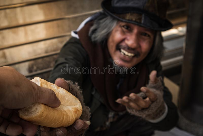 Die Hand, die Brot geben oder die Nahrung, um hungrigen obdachlosen Mann zu machen haben glückliches Gesicht stockfotos