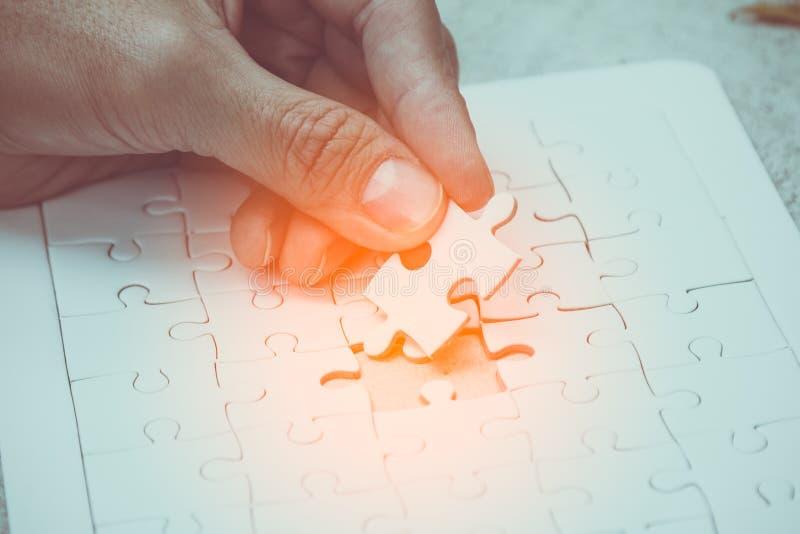 Die Hand, die das Teil der weißen Spannvorrichtung hält, sah Puzzlespiel und das Setzen, um freien Raum auszufüllen lizenzfreie stockfotografie