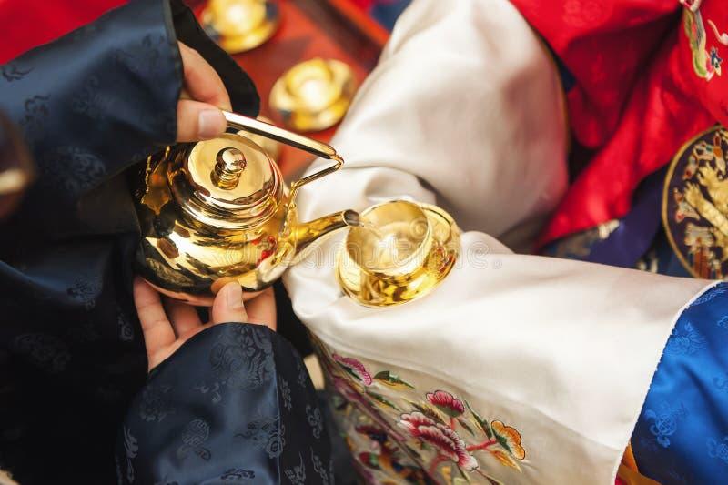 Die Hand, dass der Bräutigam die Braut gibt, um dem koreanischen traditionellen Alkohol zu folgen stockfoto
