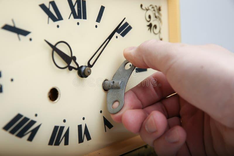 Die Hand, die den Wind-oben Schlüssel in der Uhr hält lizenzfreie stockbilder