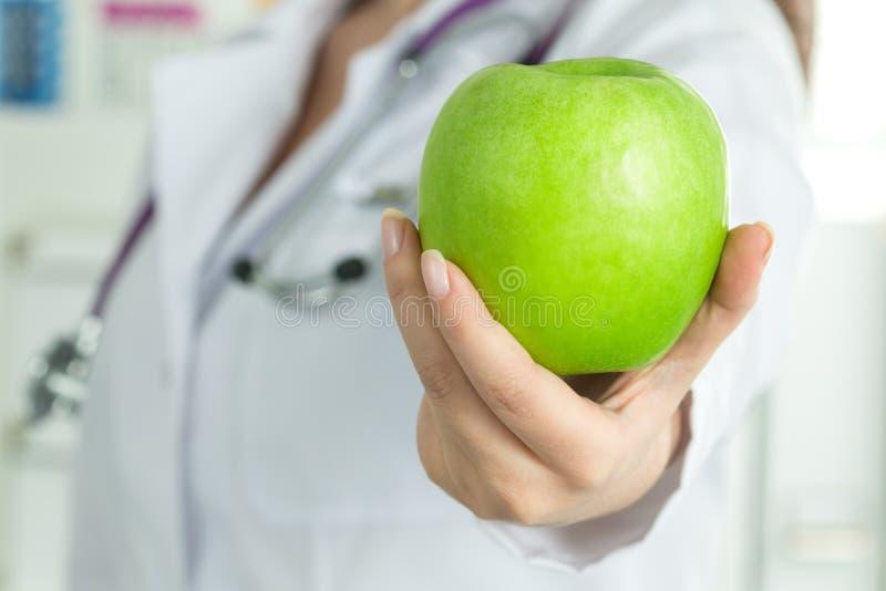 Die Hand der Ärztin, die frischen grünen Apfel gibt lizenzfreies stockbild