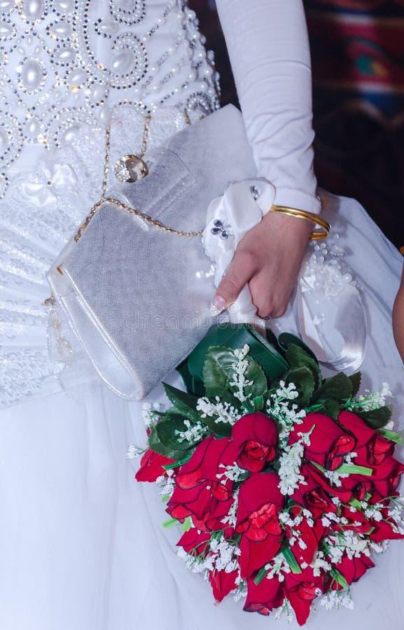 Die Hand der Braut in einem weißen Kleid mit einer Handtasche und ein Blumenstrauß von frischen roten Rosen lizenzfreies stockbild